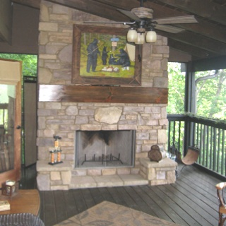Outdoor fireplace on mountain cabin deck.