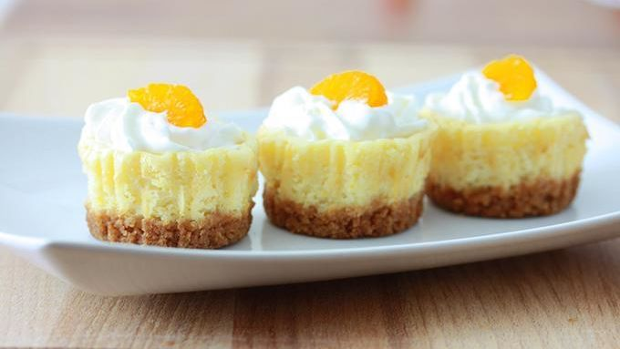 """These mini mandarin cheesecakes get an extra """"oomph"""" of citrus flavor from the tangy orange zest mixed in the batter. The subtle hint of cinnamon from Cinnamon Toast Crunch™ complements the orange nicely."""