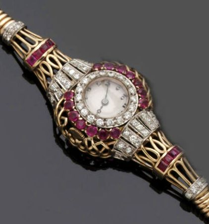 1924 ruby and diamond cocktail watch. The circular white enamel dial with black Arabic numerals, the bezel with inner border of brilliants, and edged by round mixed-cut rubies, within pierced wire work surround, between shoulders of single-cut diamonds and calibré-cut rubies, on a gas pipe-link sprung bracelet, the watch head case hallmarked for 18ct gold, import mark for London 1924, mounted into later watch setting, length 17cm.