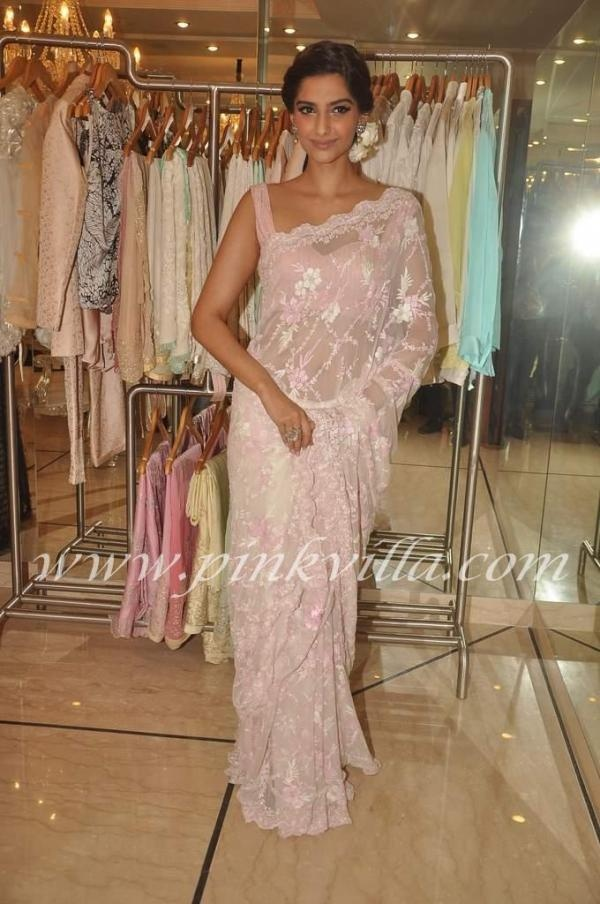 Actress Sonam Kapoor looks very pretty in a pink, champagne exquisite saree with delicate work and sleeveless blouse....the hair do with a white flower gives her that retro look....