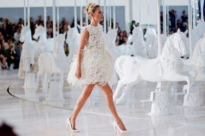 Marc Jacobs ha colocado muy alto a la firma de Louis Vuitton en la Semana de la moda en Paris presentando una colección para la primavera-verano 2012 con mucho lujo y glamour.Con una puesta en escena espectacular ya que ha colocado un tiovivo que gira en la pasarela para una industria con constante movimiento donde todo regresa al tiempo. La colección prêt-à-porter es el de una mujer bella, impoluta del principio de la década de los 60, con una amplia variedad de trajes de falda y chaqueta…