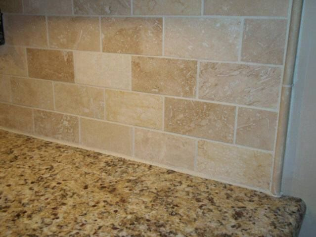 Venetian gold granite with a simple travertine subway tile backsplash with pencil strips accents - Backsplash designs travertine ...