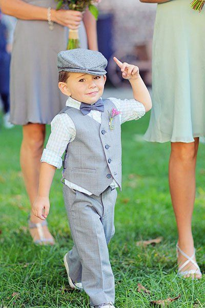With his newsboy cap, checkered vest and pants, and classy bow tie, this ring bearer is feeling his stylish look.