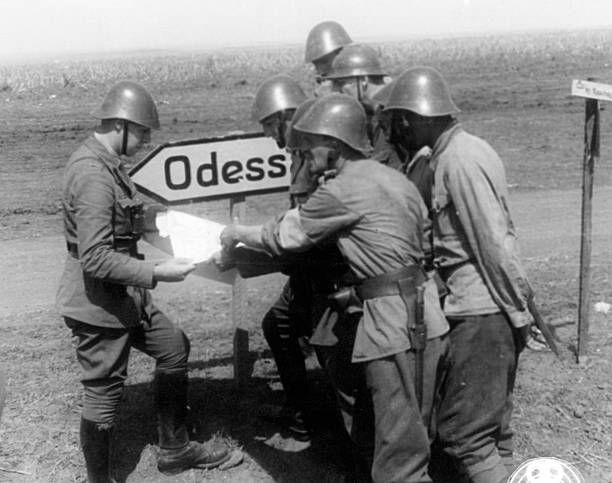 Romanian soldiers studying a map next to a road sign that shows the way to Odessa. Ukraine, August 1941 - pin by Paolo Marzioli