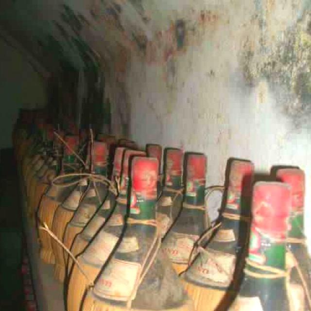 Chianti wine bottles collecting dust in the cellar at castello del trebbio.