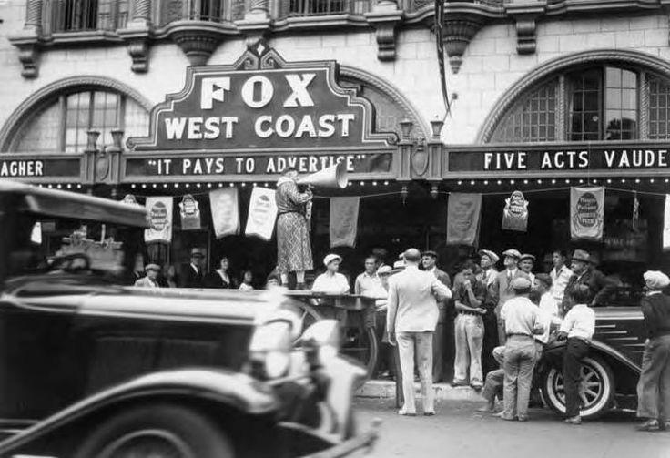 "Fox West Coast Theater on 308 N. Main. A crowd is in front of the theater listening to a man with a megaphone who stands on a flat wagon in front of the building. Banners for ""Players and Patrons Jubilee Week"" are strung across under the marquee. Santa Ana, California. 1930s."