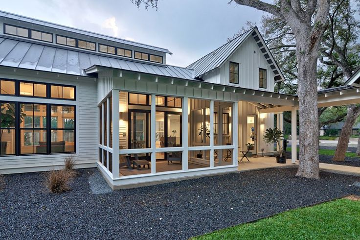 Modern farmhouse screened in porch with standing seam roof, board and batten siding, and hardscape designed by Tim Brown Architecture.