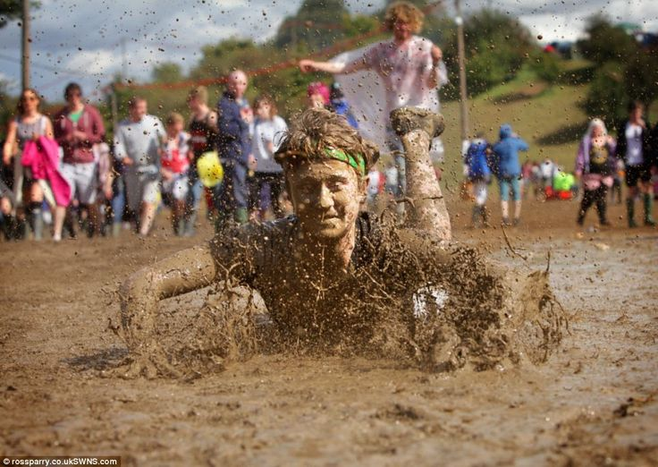 A young man dives through the mud at Leeds Festival, making the most of the wet and windy ...