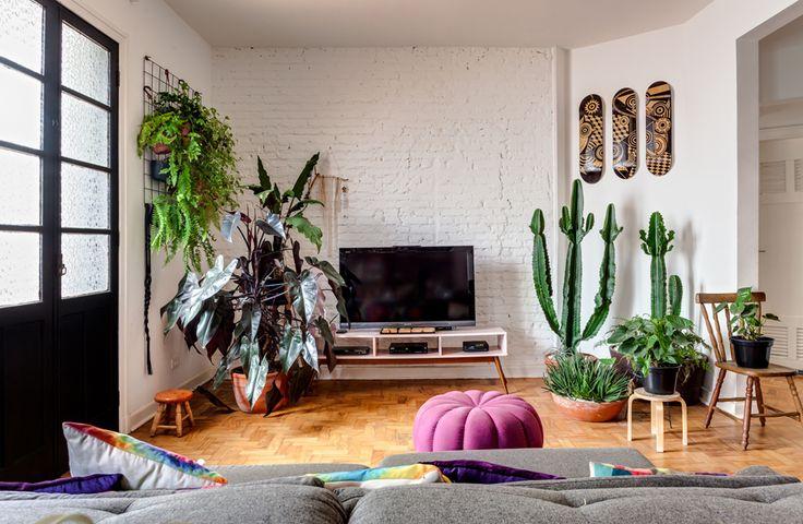sala de estar com parede de tijolinhos brancos, cactos, jardim vertical feito com grade e piso de tacos