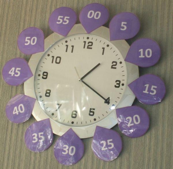 Transformation de mon horloge de classe grâce à des pétales de minutes fabriqués sous word (Malheureusement, la moquette murale n'a pas voulu en prendre de la graine :p !)