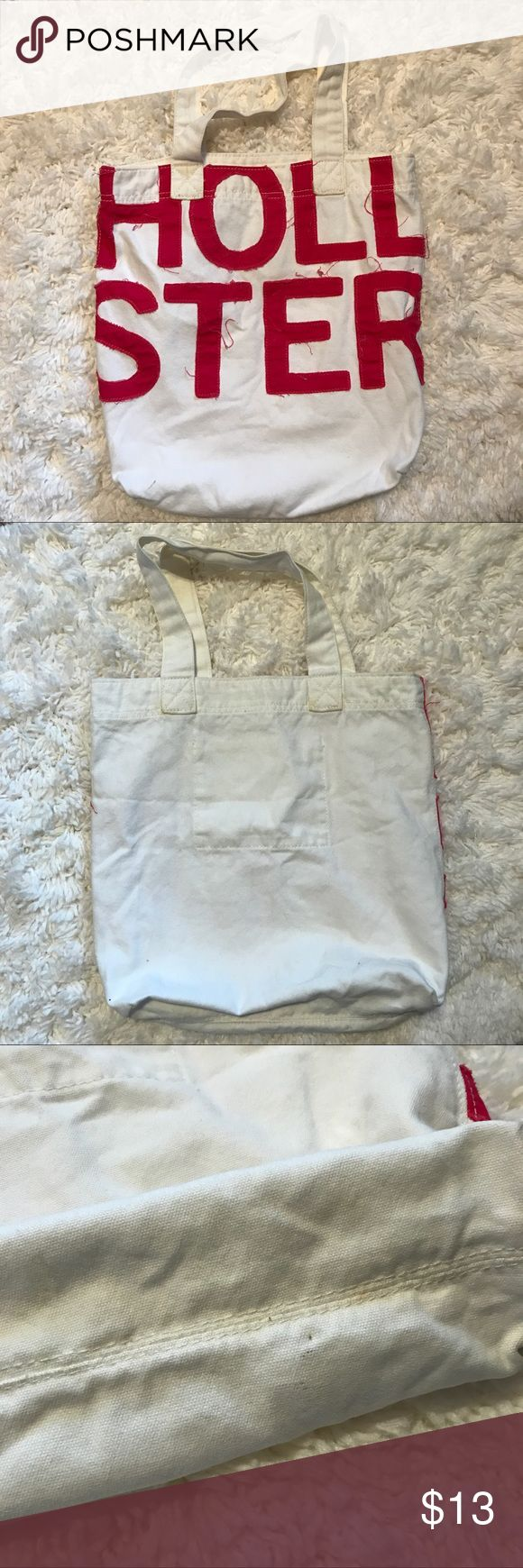 """Hollister Tote Bag Very gently used cream colored Hollister Tote Bag (with pink lettering). There are a few small stains. Perfect for carrying books, school supplies, everyday items or even travel! In great condition! Make an offer!!   Dimensions: 14""""X11""""x4"""" Hollister Bags Totes"""