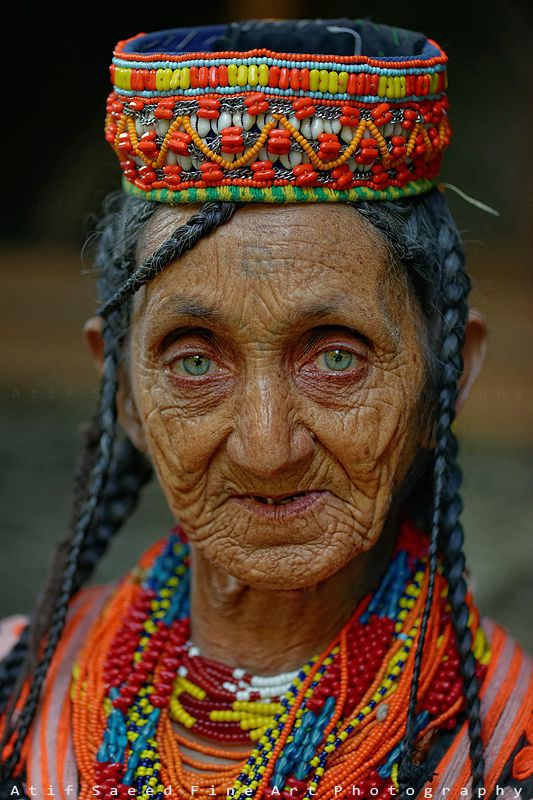 An elderly woman from Pakistan with an impassive expression, yet intense pale…