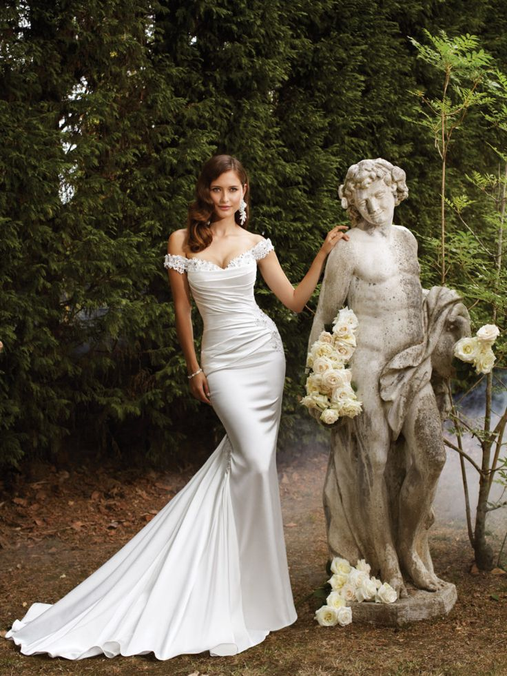 Sophia Tolli - Y21370 – Magnolia - Satin sheath wedding gown with corset back, a modern day goddess-worthy gown in shimmer satin, Magnolia boasts a stunning sheath silhouette with hand-beaded lace sweetheart neckline and off-the-shoulder straps. The draped bodice and lace appliqués on the hip set off the figure skimming skirt that features a gentle sweep train adorned with lace appliqués. A corset back closure trimmed with matching appliqués Sizes:  0 – 28Colors: Diamond White, White