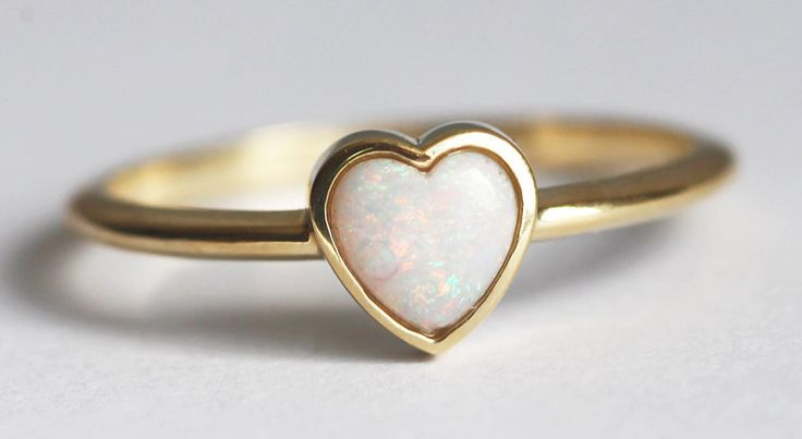 """A dainty opal <a href=""""http://go.redirectingat.com?id=74679X1524629&sref=https%3A%2F%2Fwww.buzzfeed.com%2Fsarahhan%2Fit-aint-all-diamonds&url=https%3A%2F%2Fwww.etsy.com%2Flisting%2F252928645%2Fopal-heart-ring-opal-solitaire-ring&xcust=4422693%7CBFLITE&xs=1"""" target=""""_blank"""">ring</a> that'll win over your real heart."""