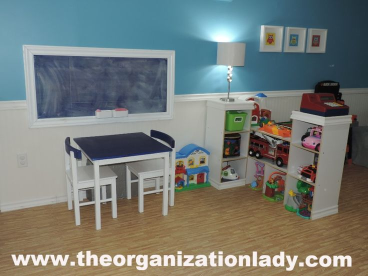 Sheet metal, fiberboard, trim and chalk paint were used to create this custom magnetic chalkboard with a chalkboard table top painted to match. This multi-use area is perfect for snack time! 3 sets of 3 cube shelving put together unconventionally were used to accommodate the larger toys and help to divide the space.