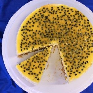 A birdseye view of a cheesecake topped with lots of passionfruit seeds