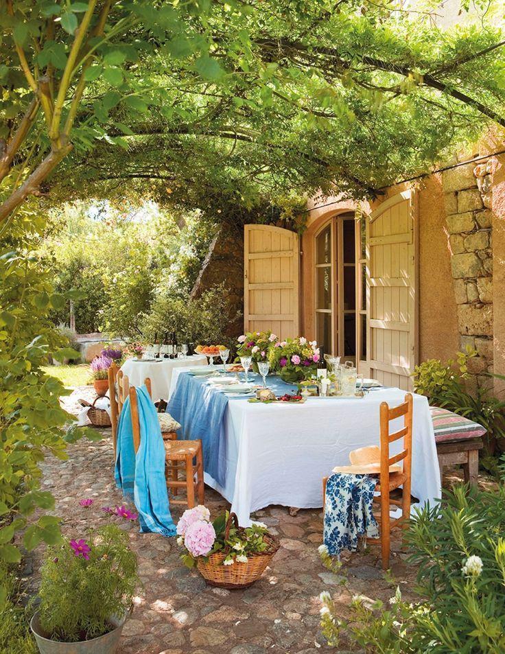 Comedo exterior bajo pérgola de hierro con enredaderas, mantel blanco y azul y flores 369187 | https://lomejordelaweb.es/