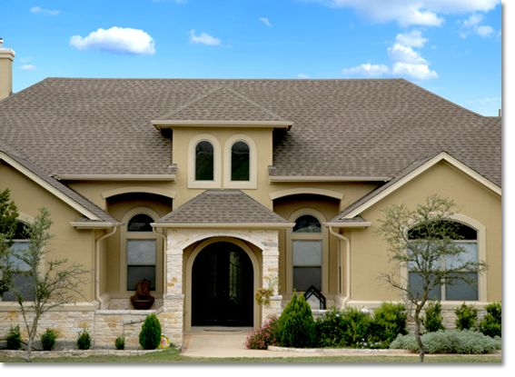 stucco and stone home with light color stucco wrapped windows