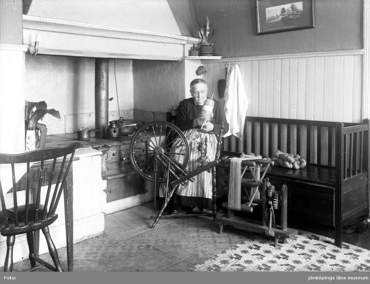 En äldre kvinna sitter vid sin spinnrock. Till vänster är eldstaden med en järnspis och till höger står en kökssoffa av trä där det ligger färdigspunna garnhärvor. Sweden.