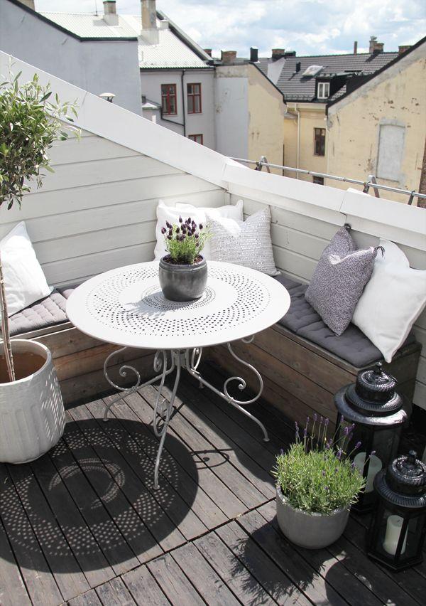Une petite table et une banquette avec des coussins pour un balcon cosy.