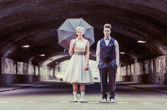 Brautpaar im 50er Jahre rockabilly Look, Petticoat Brautkleid mit grauem Tüllrock, Regenschirm in grau mit weißen Punkten und passenden Accessoires für den Bräutigam  (www.noni-mode.de - Foto: Manuel Thomé)