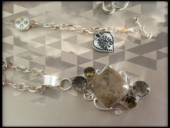This handcrafted, Unique, one of a kind Fossil Coral & Smoky Silver Pendant Necklace from Simply Charmed Jewelry is an Original! It measures 20.5 from end to end and is full of gorgeous glass beading and unique flower spacers. I finished it off with more flowers on the Unique