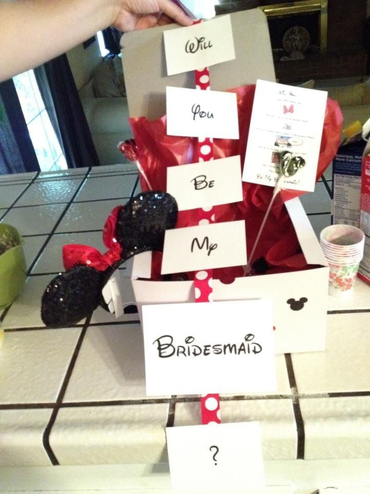 "Will you be my Bridesmaid?? (Disney Wedding) On the outside of the box it is covered with red and black Mickey heads! In the inside... I printed out ""Will you be my Bridesmaid?"" cards and glued them to a red and white Polk a dots ribbon!  Mickey Mouse Lollipops and Chocolates! A little Minnie Mouse key chain! And of course MINNIE MOUSE EARS!!!"