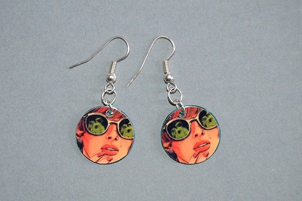 Earrings made of plastic checkers chips and pictures of a comic book-like woman. Minka / www.madeby.fi