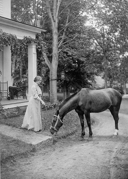 Helen Keller, full-length portrait standing on lawn holding reins to a horse , c 1907 . Via Library of Congress