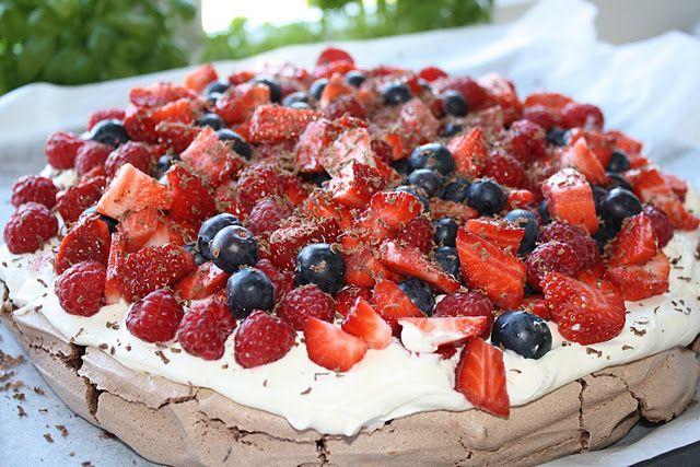 Chokolade-pavlova Ca. 8-10 personer Ingredienser 6 æggehvider 300 g sukker 3 spsk kakao pulver, sigtes 1 tsk balsamico eller rødvinseddike 50 g mørk chokolade, finthakket Fyld 1/2 liter piskefløde 500 g jordbær 125 g hindbær 125 g blåbær 2-3 spsk revet mørk chokolade Fremgangsmåde Forvarm ovnen til 180 grader. Tegn en cirkel på ca....Læs mere »