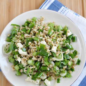"""Spelt is een stoer """"oer""""graan en een perfecte basis voor frisse bijgerechten zoals deze salade met feta, munt en lente-uitjes. De milde honing-citroendressing met knoflook maakt het af. Voeg voor een leuke variant op dit recept wat geroosterde pecannoten of in citroensap geweekte rozijnen toe!"""