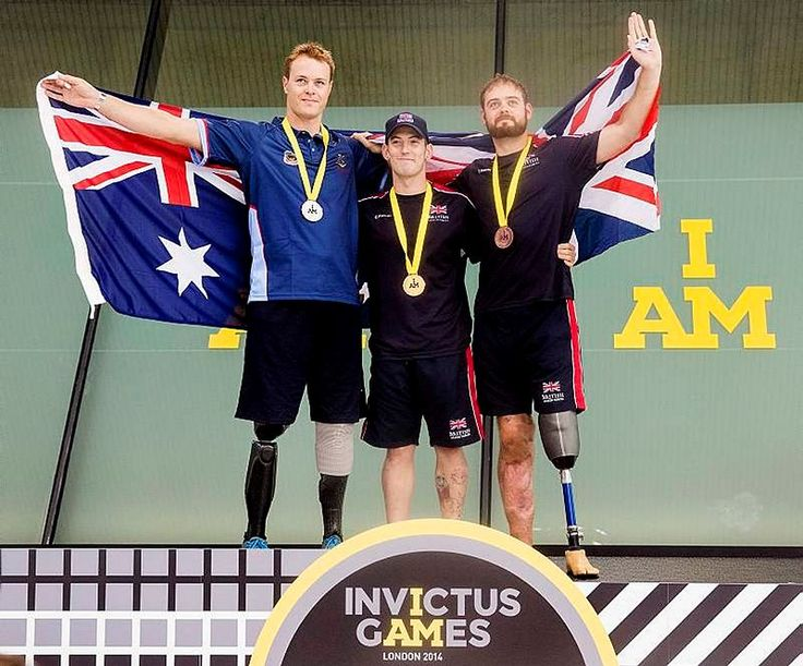 Former soldier Curtis McGrath (left) displays his silver medal for swimming at the Invictus Games in London on September 14.