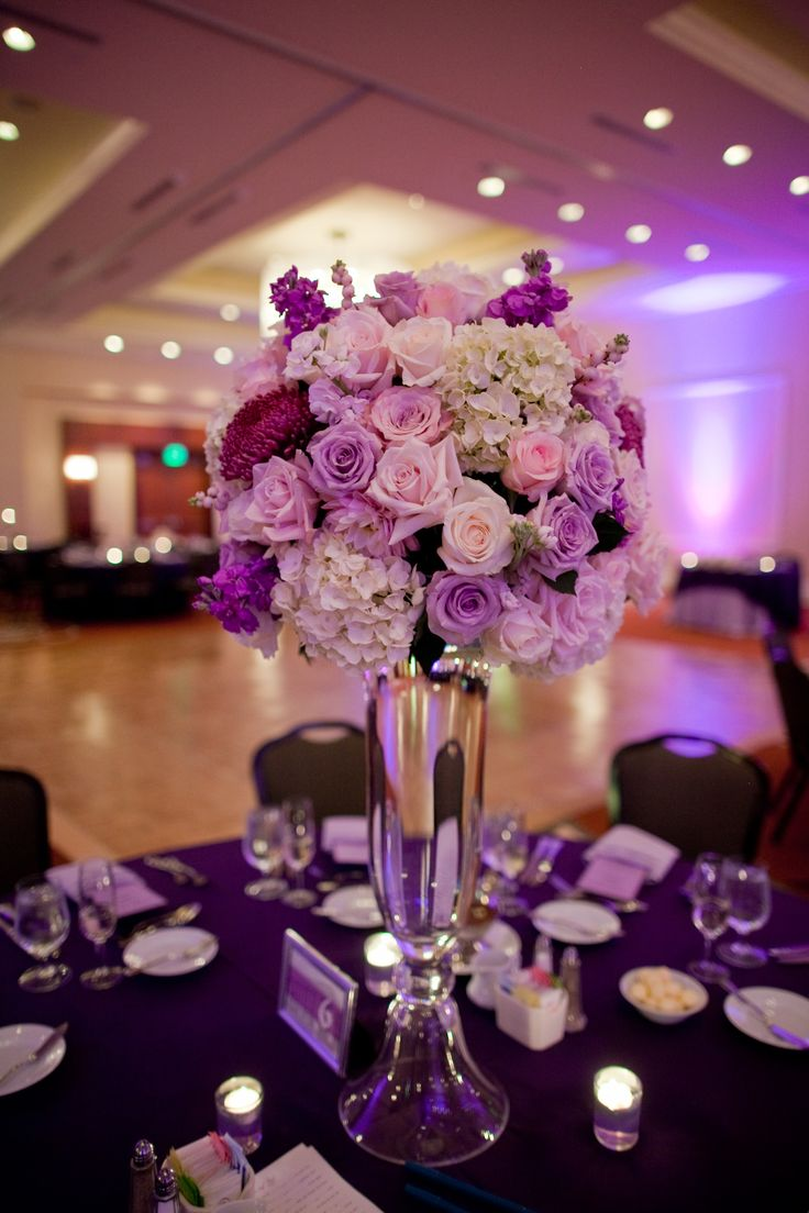 Tall centerpiece with white purple and pink flowers in