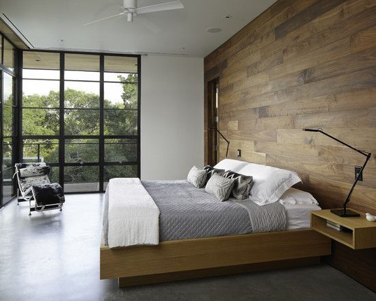 This bedroom is very stylish with its large wood wall to give the room an earthy feel and the modern flooring contrasts it well.