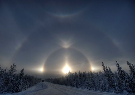 """""""A photographer in Finland was at the right place at the right time and  got to experience a very rare sight. Most of us have seen sun pillars,  or sundogs, or even a halo around the sun, well this man saw 13  different optical phenomena all at once. Ice crystals that create  colored or white arcs/spots in the sky produce these types of  atmospheric phenomena. Many are usually near the sun but others are  scattered elsewhere. The particular shape and orientation of the  crystals are respon"""
