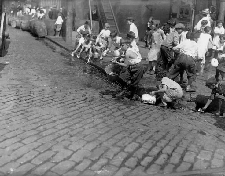 Children scramble on Van Brunt and Sackett Streets to scoop up wine from the gutters and sewers after it is dumped by Prohibition Agents.