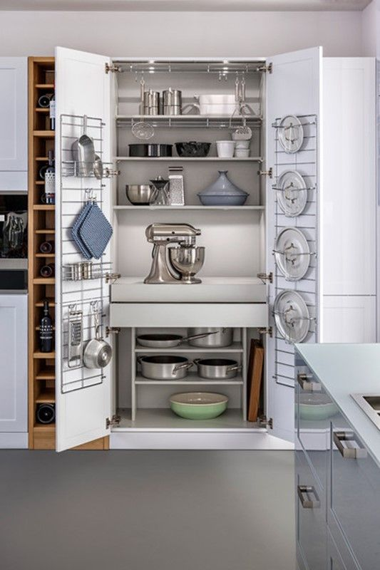 White, large chef's pantry built for storing kitchen appliances, pots and pans. Photo by Photo by Leicht Küchen AG