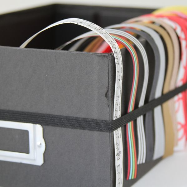 Use a shoebox or photo box with elastic around the outside to keep ribbon neatly organized and handy.