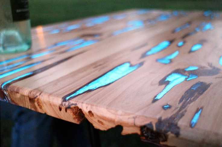 """Maker Mike Warren has created a beautiful wooden table with glow in the dark inlays that illuminate after being exposed to light. For his table, Warren used a sheet of pecky cypress, a special cypress wood which contains rotten sections that can be easily removed. He filled the cavities with phosphorescent powder mixed with clear resin."""