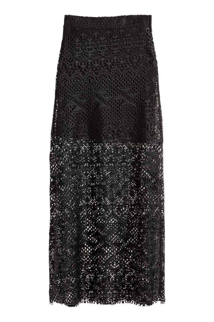 Lange kanten rok: Een lange rok van opengewerkt kant met een hoge split aan de zijkanten. De rok heeft elastiek in de taille en is gevoerd met een korte tricot onderrok.