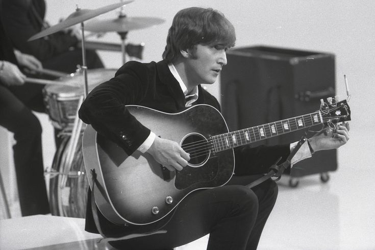 John LENNON; of the Beatles, tuning guitar (Gibson J160E acoustic) during the filming of 'A Hard Day's Night' at the Scala Theatre