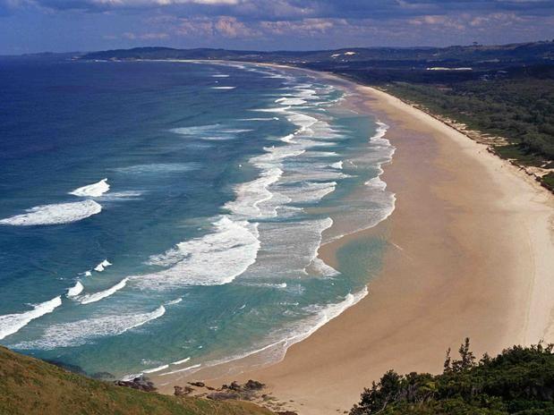 """Byron Bay Beach Ponto mais oriental da Austrália, Byron Bay já está longe de seus anos de cidade """"hippie"""" e está cada vez mais desenvolvida, com cafés e hotéis modernos. A localização da praia de Byron Bay Beach faz com que ela tenha ondas excelentes que atraem surfistas do mundo inteiro."""