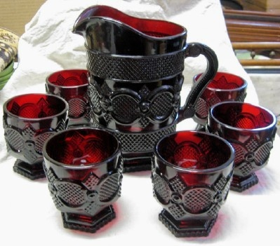 "AVON 1876 CAPE COD, RUBY RED GLASS, WATER PITCHER PLUS 6 FOOTED TUMBLERS 3.75"" high."