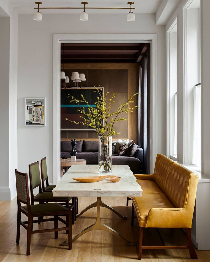 The table and chairs in the dining area of a family loft in Manhattan are by BDDW; the custom ceiling fixture is by O'lampia, the flooring is white oak, and the room is painted in Benjamin Moore's Intense White. | Photo: @ericpiasecki; Design: @dumais_inc