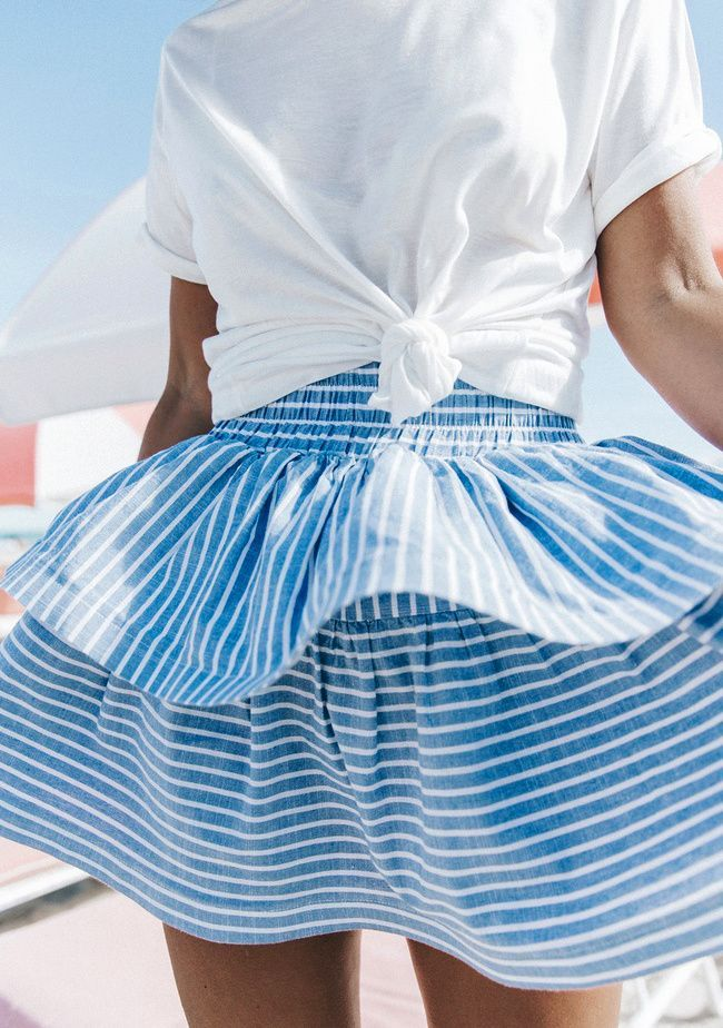 Striped short skirt and white blouse. Fashion for summer.