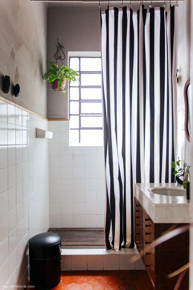 Banheiro tem meia parede revestida de azulejo e meia parede pintada de cinza.