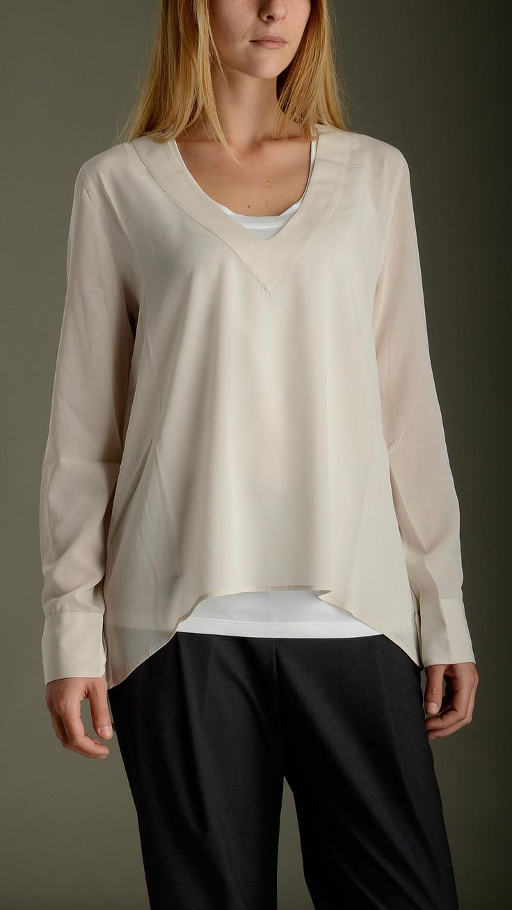 Blusa color vaniglia realizzata in organza di seta abbinata ad una canotta bianca realizzata in jersey di cotone, maniche lunghe, fondo asimmetrico, polsini regolabili con bottone, vestibilità comoda, 95% seta 5% elastan    .