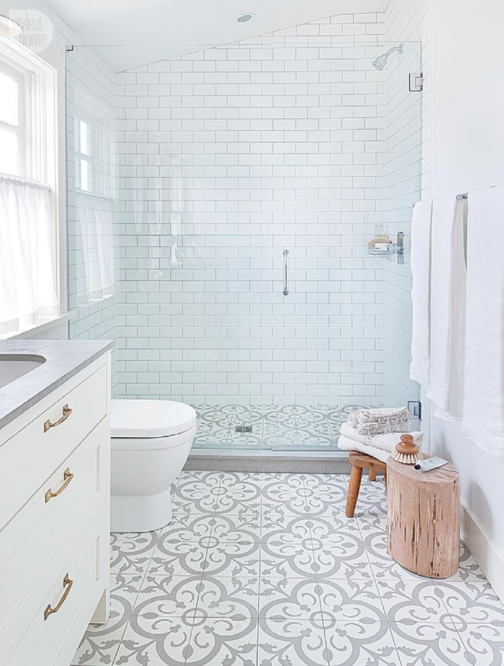 A white bathroom with a patterned tiled floor.   I like the tree trunk... I have two outside my front door