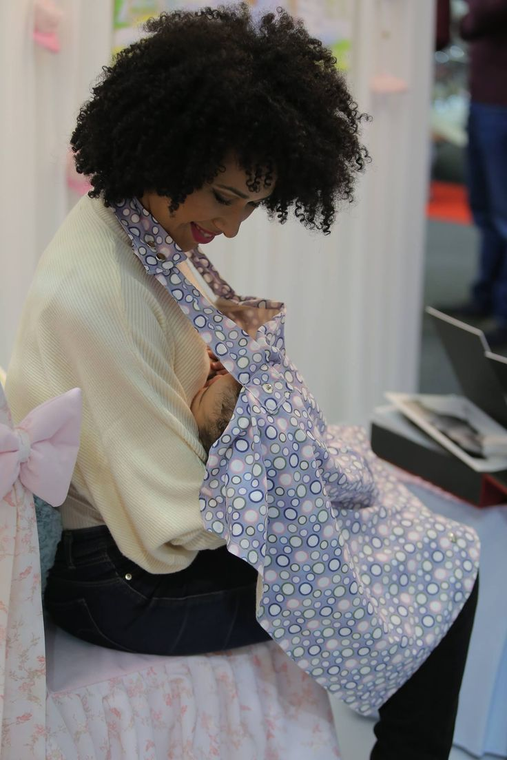 Breastfeeding apron in blue cotton tissue with details of variables collours balls of Holland source, with coating also in beige cotton and spring metal pressure.Ref. AVAM10 Model: Djeissica Barbosa (Miss S. Tomé e Príncipe 2014) and her daughter.  Photographer: Pedro Miranda