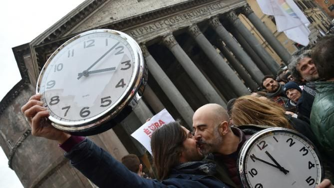 "Supporters of same-sex civil union kiss holding alarm clocks ""to wake up Italia"" on January 23, 2016 near the Pantheon in central Rome"